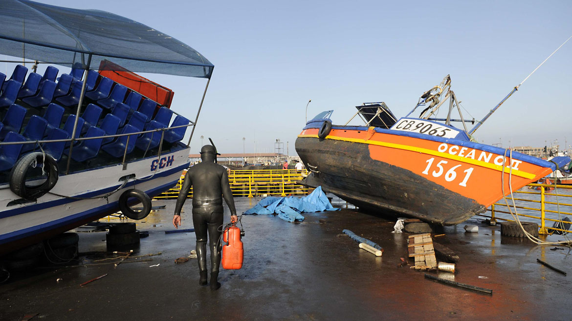 A diver walks between boats washed inland after a tsunami hit the northern port of Iquique