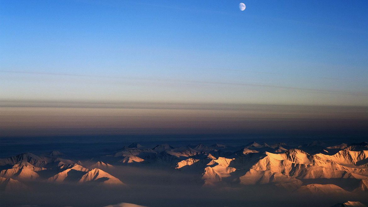 The moon is seen north of the Fram Strait in northeast Greenland in this NASA Operation IceBridge picture