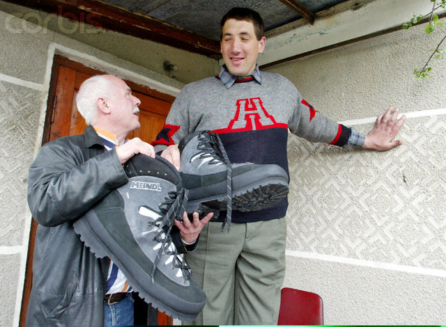 German shoemaker Wessels presents a pair of shoes to Ukraine's Stadnyk near his house in Podolyantsi in Ukraine's Zhytomyr region