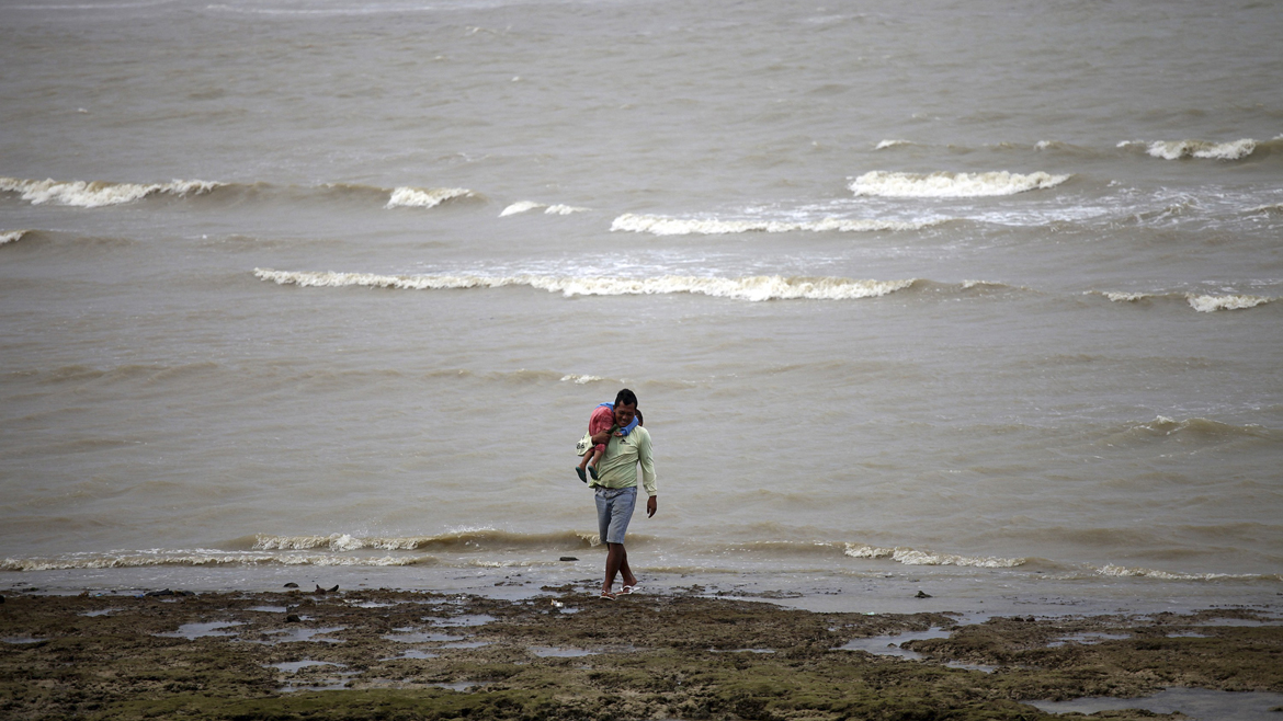 A man carries his daughter as he walks along the shore in the coastal area of Poblacion village in central Philippines