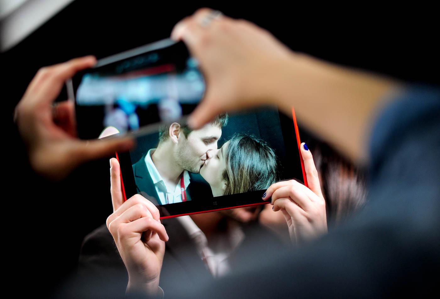 Una persona toma una foto de una tablet, que toma la imagen de una pareja besándose durante el Mobile World Congress, en Barcelona