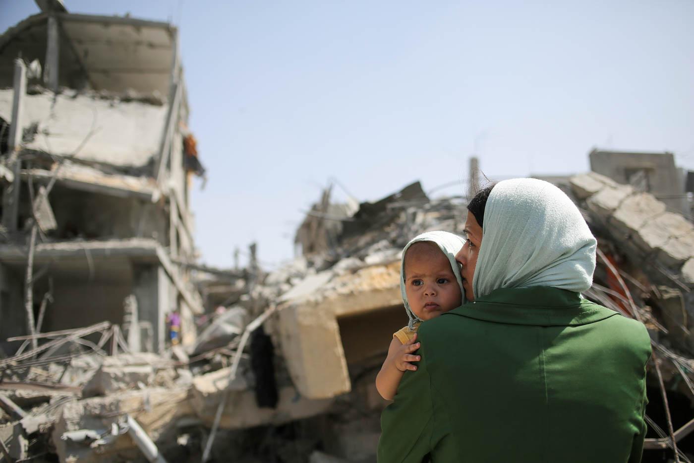 Una madre palestina besa a su hijo entre los escombros de su higar en Beit Hanun, en el norte de la Franja de Gaza