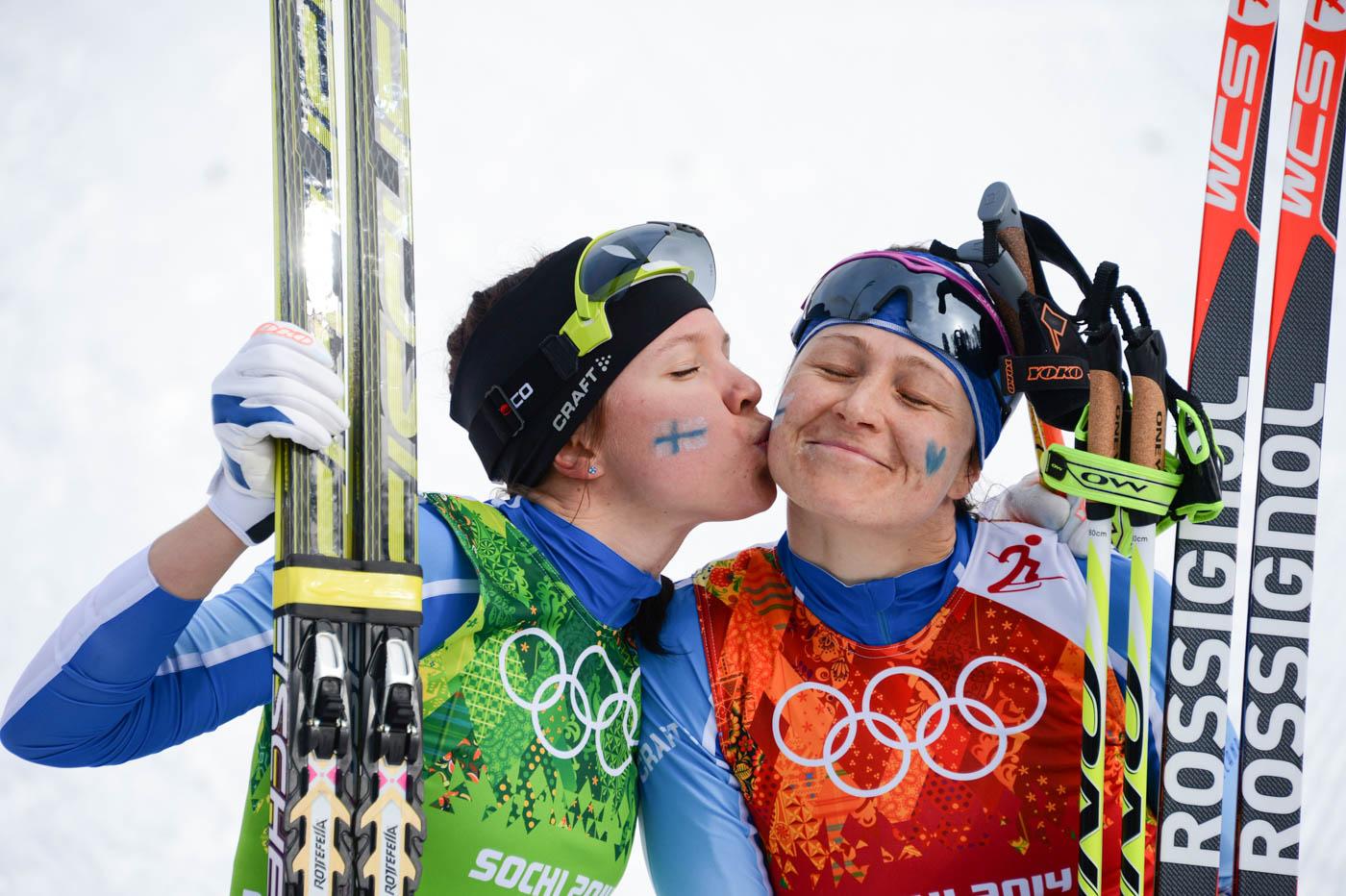Las medallitas de plata de Finlandia, Kerttu Niskanen y Aino-Kaisa saarinen se besan luego de ganar segundo lugar en esquí de fondo en Sochi 2014