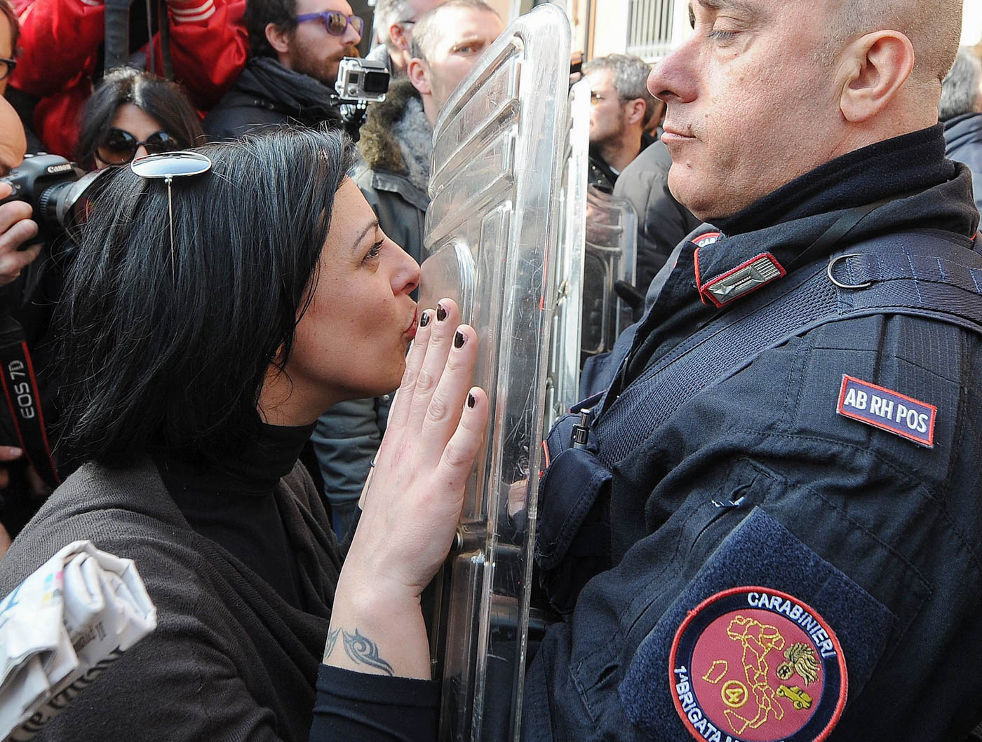 una mujer besa el escudo de un policía durante la visita del Primer Ministro de Italia, Matteo Renzi, a una escuela