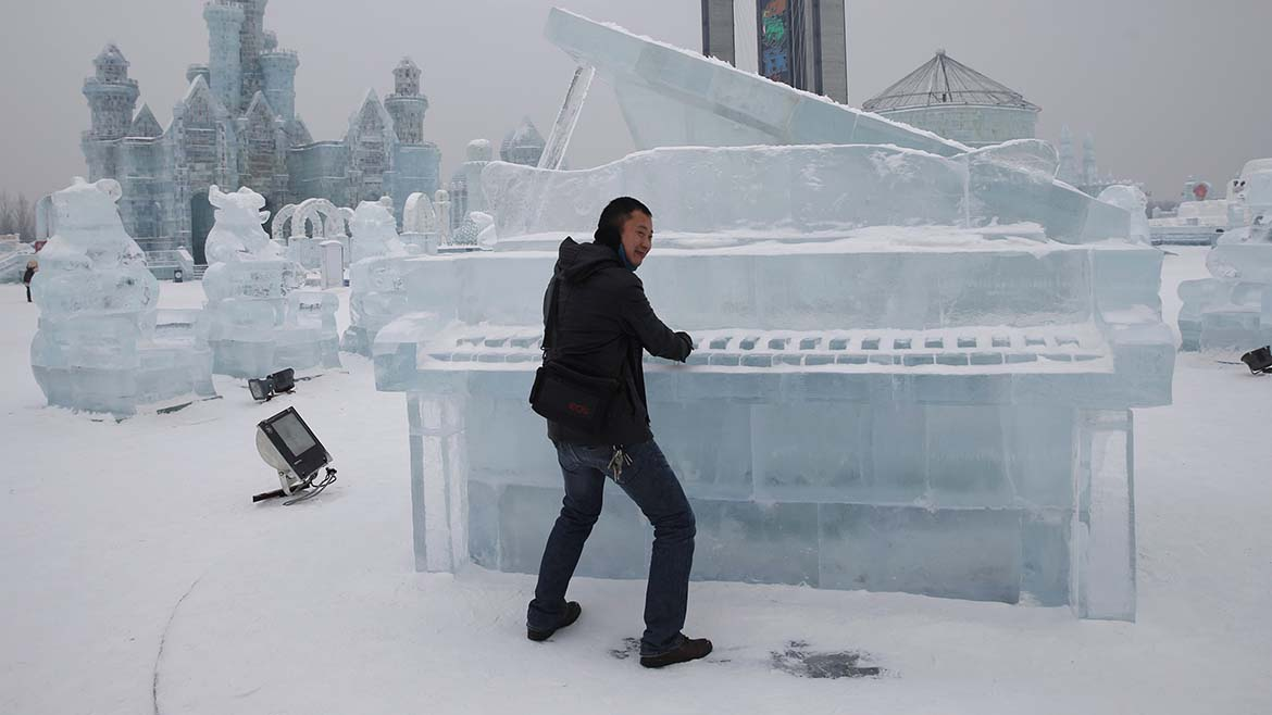 A visitor has his picture taken with a piano-shaped ice sculpture ahead of the 31st Harbin International Ice and Snow Festival in the northern city of Harbin