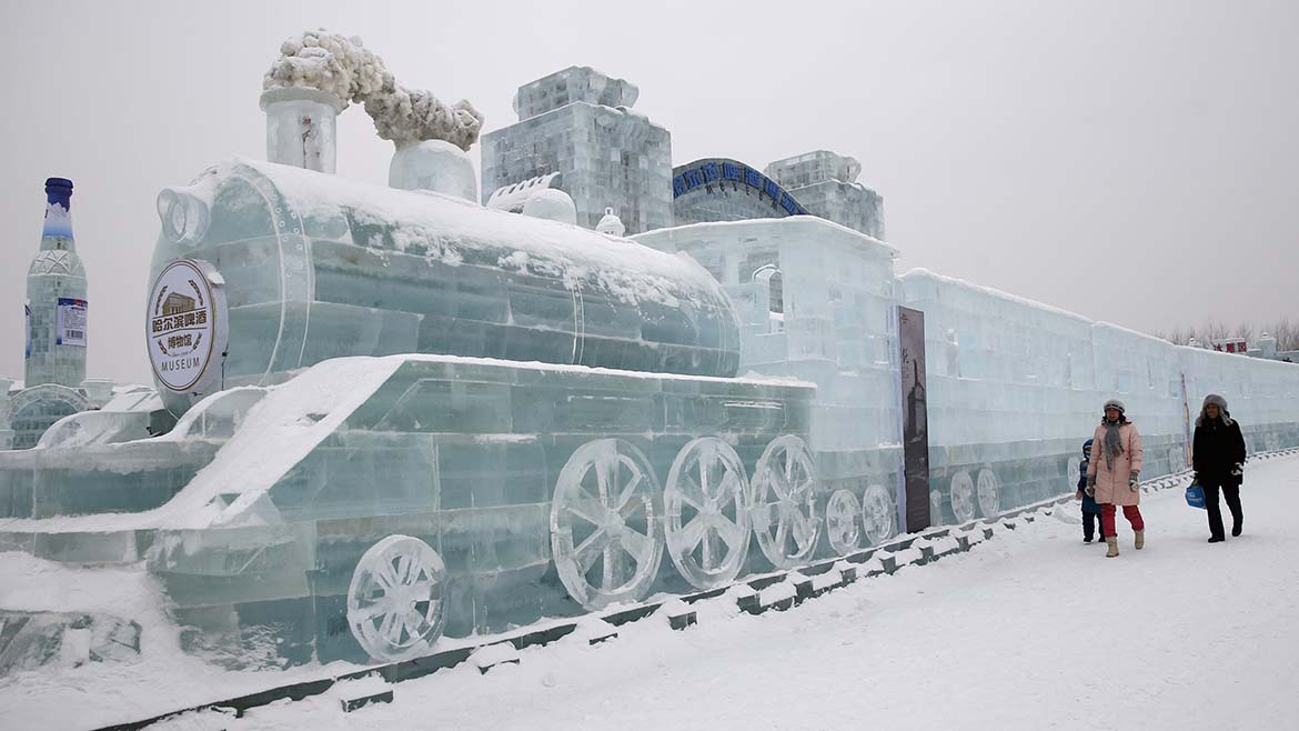 Visitors walk past a train-shaped ice sculpture ahead of the 31st Harbin International Ice and Snow Festival in the northern city of Harbin