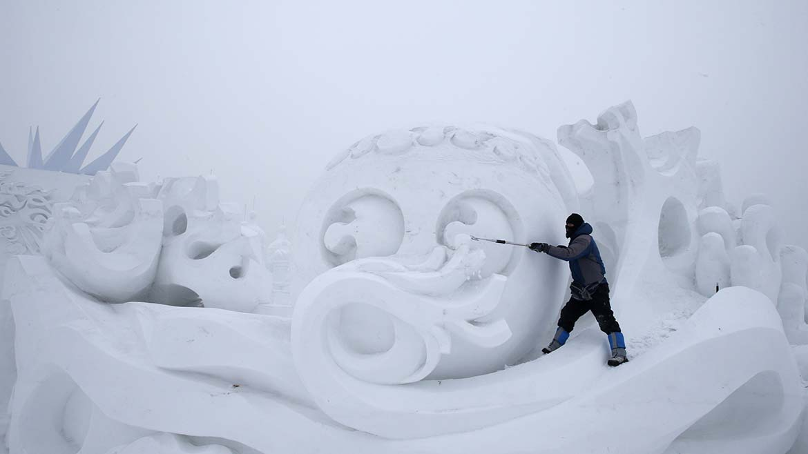 A worker polishes a snow sculpture ahead of the 31st Harbin International Ice and Snow Festival in the northern city of Harbin