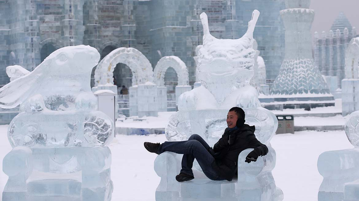 A visitor takes a picture with an ice sculpture ahead of the 31st Harbin International Ice and Snow Festival in the northern city of Harbin