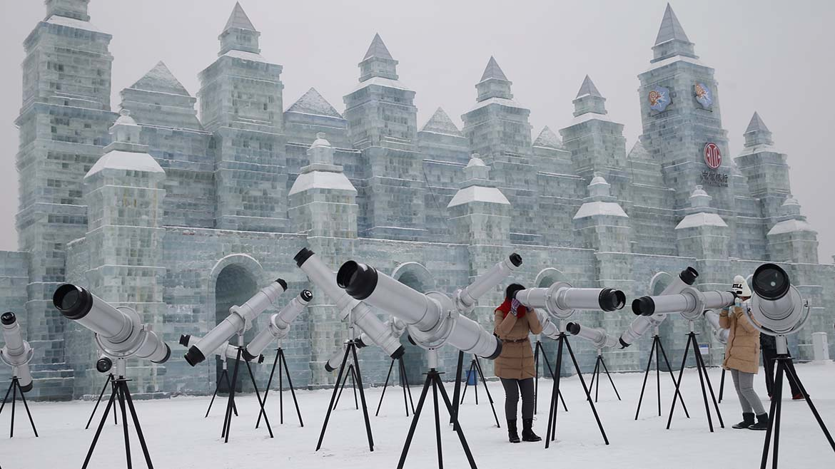 Visitors use kaleidoscopes which are displayed with ice sculptures ahead of the 31st Harbin International Ice and Snow Festival in the northern city of Harbin, Heilongjiang province