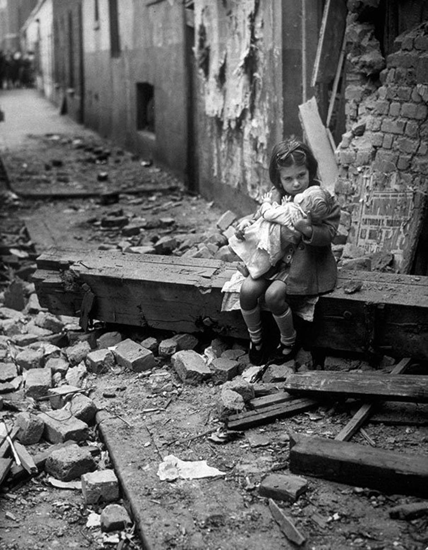 Niña con su muñeca, sentada en las ruinas de su casa bombardeada, Londres, 1940