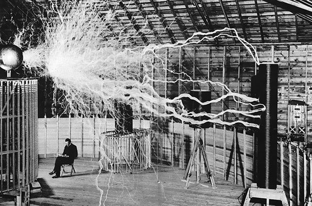 """Nikola Tesla en su laboratorio, sentado detrás de su """"Transmisor de aumento"""""""