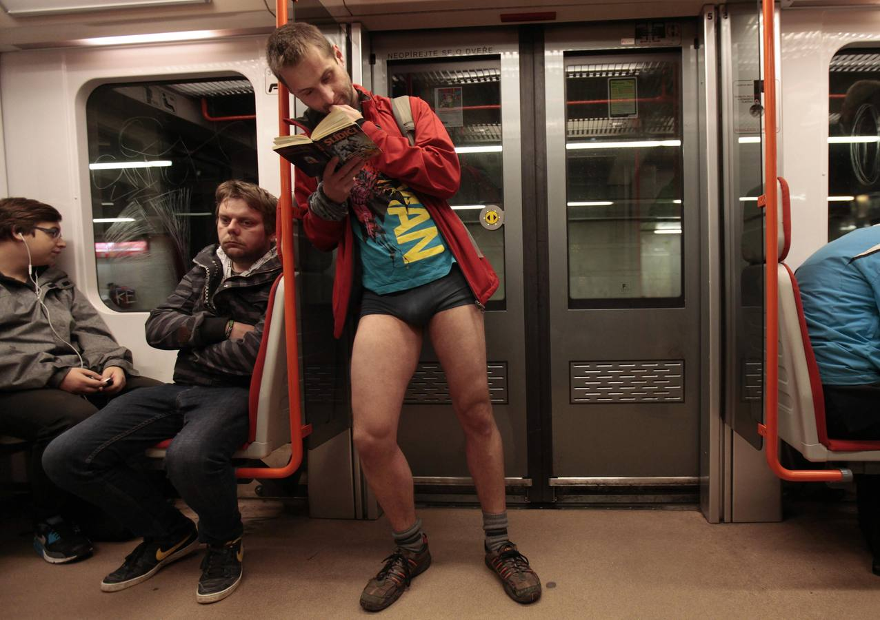 "A passenger not wearing pants reads a book as he stands in a subway train during the ""No Pants Subway Ride"" in Prague"