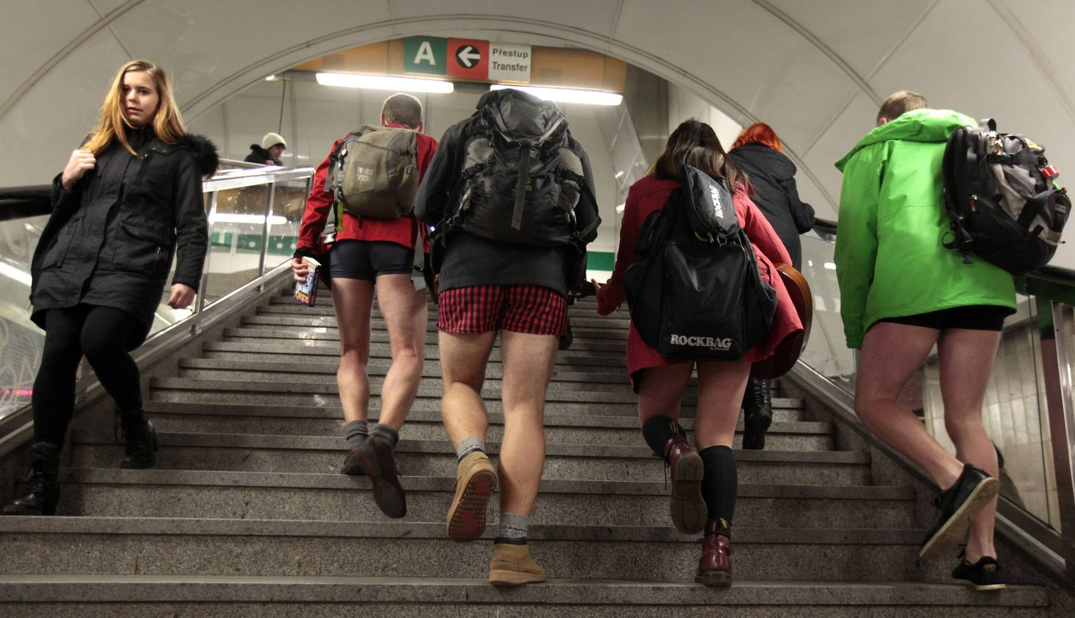 "Passengers not wearing pants walk up the stairs through a subway train transfer tunnel  during the ""No Pants Subway Ride"" in Prague"