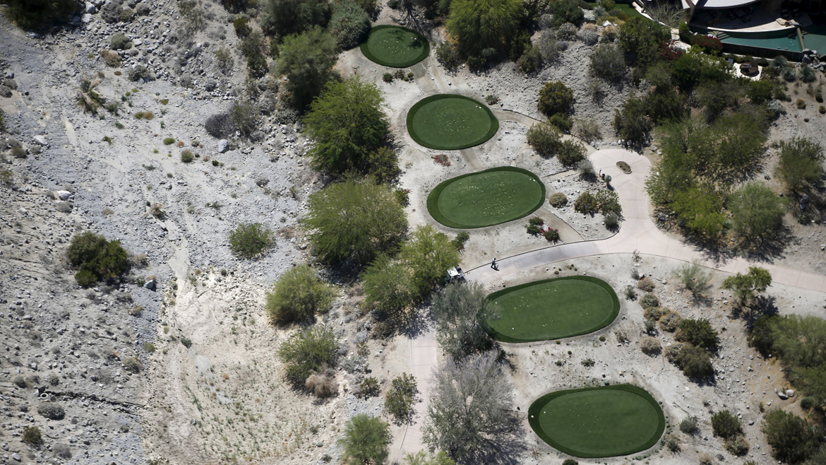 A gardener works on a golf course in La Quinta