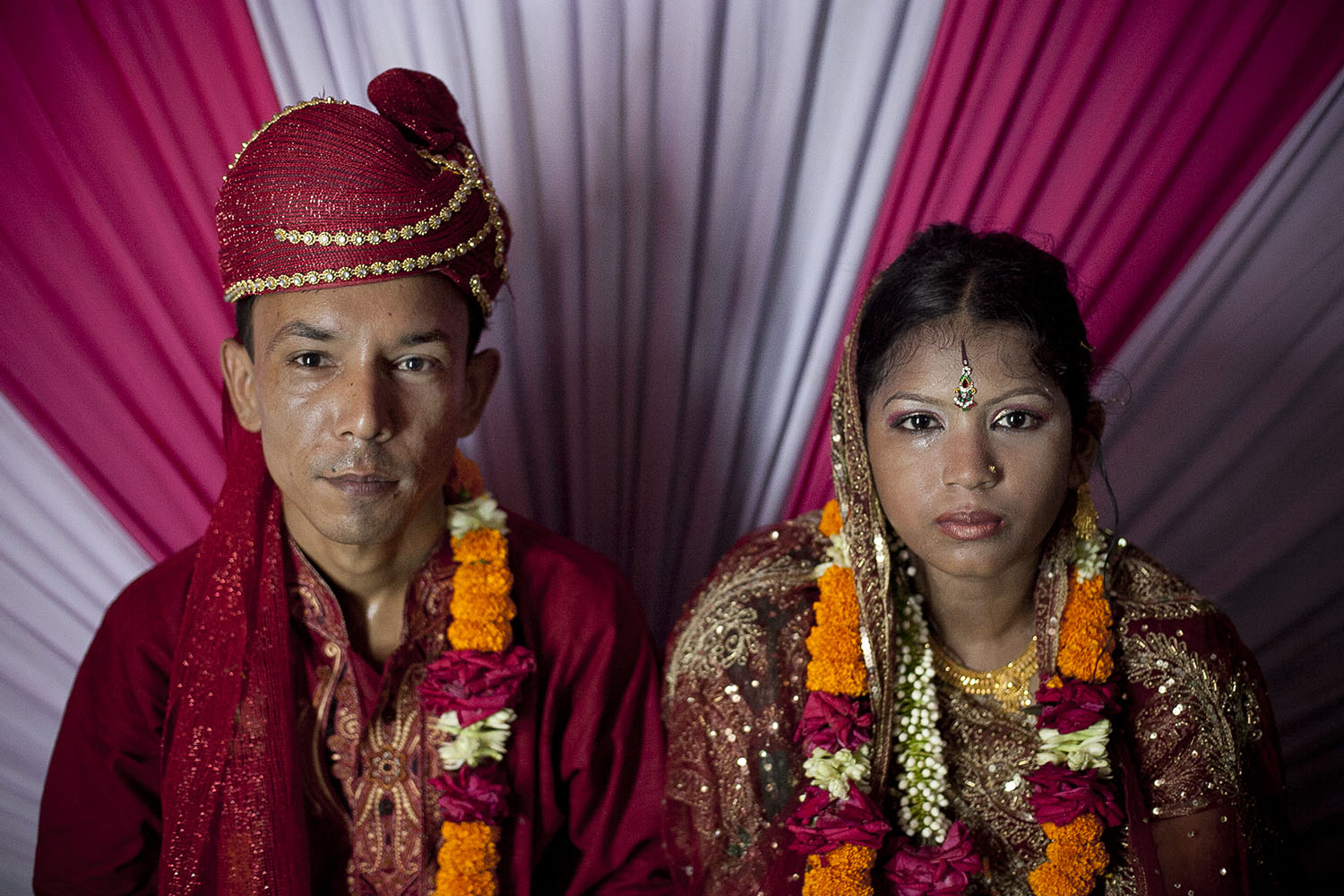 13 year old Runa Akhter sits next to her husband, 29 year old Zahrul Haque Kajal, the day of her wedding,