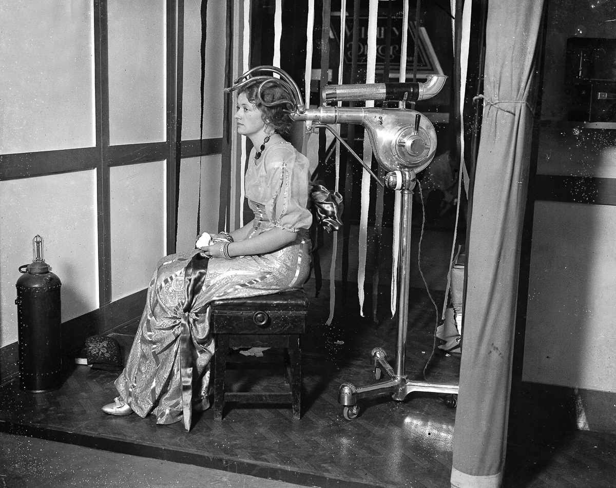 Lodon, England, 5th November, 1930, A woman tries out one of the latest types of hair drying machines seen at the hair dressing Fashion Fair held at Olympia in London