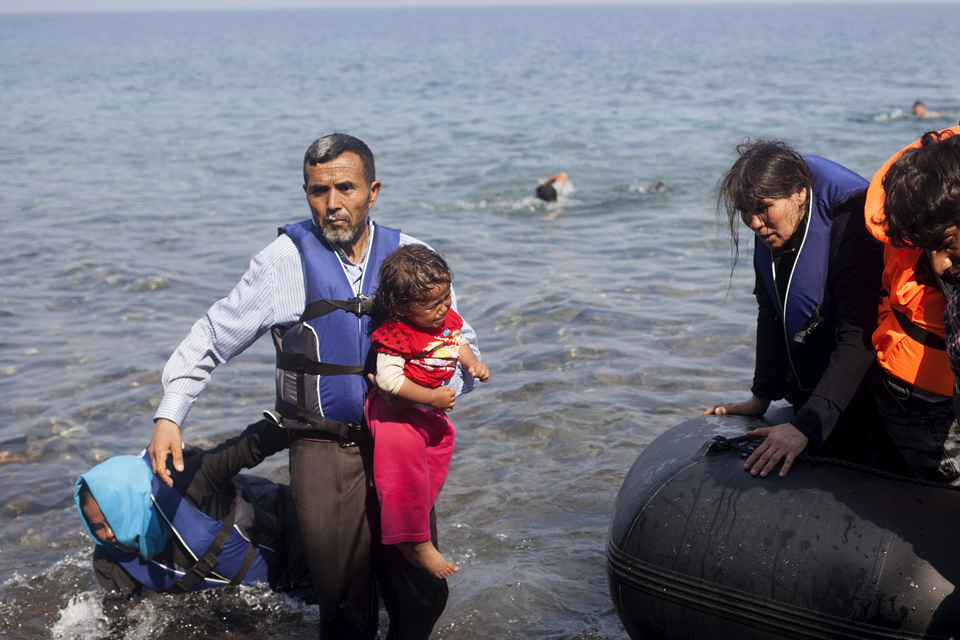 A Syrian refugee holds a baby after jumping off a dinghy after arriving on the Greek island of Lesbos