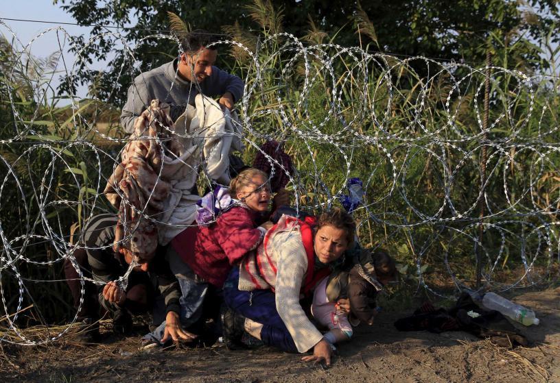 Migrantes sirios tratan de cruzar la frontera de Hungría con Serbia.