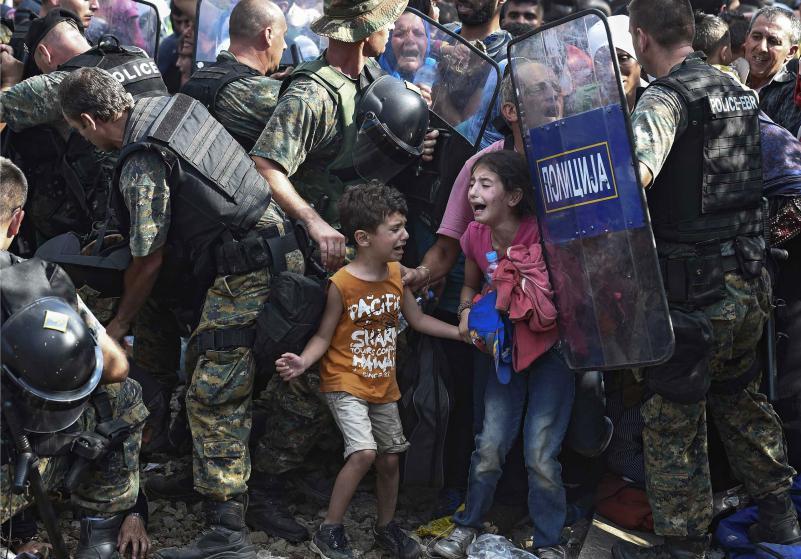 Niños lloran mientras los migrantes en la frontera griega tratan de romper un cordón militar y pasar a Macedonia