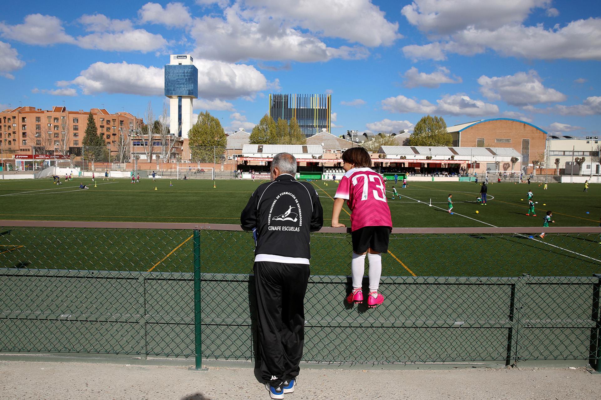 "Osama Abdul Mohsen (L), a Syrian refugee, and his young son Zaid watch a soccer training session in Villaverde, a neighbourhood in Madrid, Spain, April 14, 2016. Mohsen's story went viral after he was filmed being tripped up by a camerawoman as he fled police near the Hungarian border with Serbia last September. He was carrying his youngest son Zaid in his arms at the time, and the two fell sprawling on the ground. Footage of the incident helped bring him to the attention of a soccer training school in Getafe on the outskirts of Madrid, which found him work as a liaison officer. REUTERS/Sergio Perez     SEARCH ""REFUGEE PEREZ"" FOR THIS STORY. SEARCH ""THE WIDER IMAGE"" FOR ALL STORIES   - RTX2CXCL"