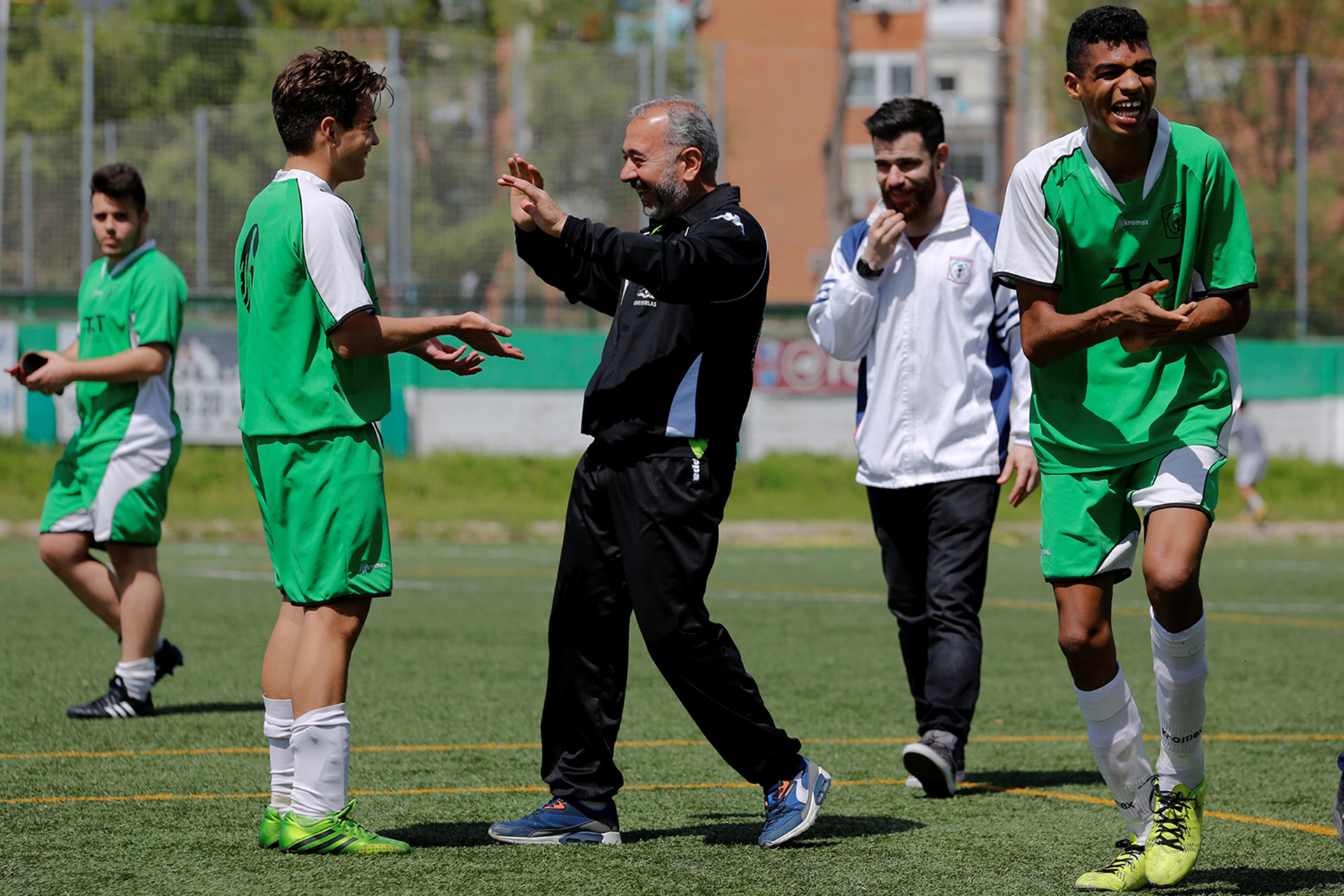 "ATTENTION EDITORS: SPANISH LAW REQUIRES THAT THE FACES OF MINORS ARE MASKED IN PUBLICATIONS WITHIN SPAIN - Osama Abdul Mohsen (C), a Syrian refugee, celebrates victory with his junior team's players after a soccer match in Villaverde, a neighbourhood in Madrid, Spain, April 24, 2016. Mohsen's story went viral after he was filmed being tripped up by a camerawoman as he fled police near the Hungarian border with Serbia last September. He was carrying his youngest son Zaid in his arms at the time, and the two fell sprawling on the ground. Footage of the incident helped bring him to the attention of a soccer training school in Getafe on the outskirts of Madrid, which found him work as a liaison officer. REUTERS/Sergio Perez     SEARCH ""REFUGEE PEREZ"" FOR THIS STORY. SEARCH ""THE WIDER IMAGE"" FOR ALL STORIES   - RTX2CXCJ"