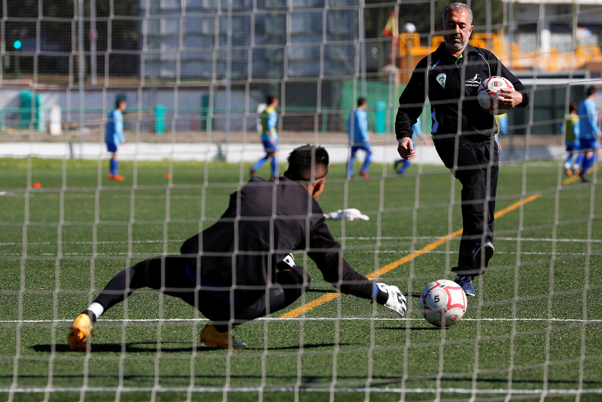 "Osama Abdul Mohsen, a Syrian refugee, warms up a goalkeeper before a soccer match with his junior team in Villaverde, a neighbourhood in Madrid, Spain, April 24, 2016. Mohsen's story went viral after he was filmed being tripped up by a camerawoman as he fled police near the Hungarian border with Serbia last September. He was carrying his youngest son Zaid in his arms at the time, and the two fell sprawling on the ground. Footage of the incident helped bring him to the attention of a soccer training school in Getafe on the outskirts of Madrid, which found him work as a liaison officer. REUTERS/Sergio Perez     SEARCH ""REFUGEE PEREZ"" FOR THIS STORY. SEARCH ""THE WIDER IMAGE"" FOR ALL STORIES   - RTX2CXCS"