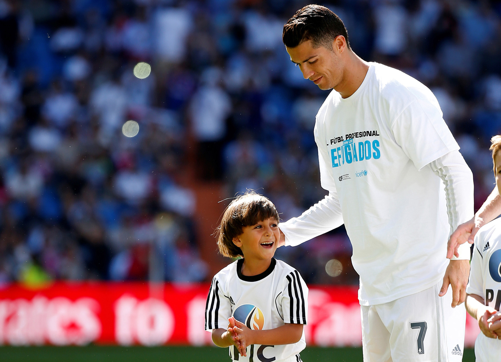 "ATTENTION EDITORS: SPANISH LAW REQUIRES THAT THE FACES OF MINORS ARE MASKED IN PUBLICATIONS WITHIN SPAIN - Zaid, son of Osama Abdul Mohsen, smiles as he stands next to Real Madrid's Cristiano Ronaldo before the Spanish first division soccer match against Granada at Santiago Bernabeu stadium in Madrid, Spain, September 20, 2015. Mohsen's story went viral after he was filmed being tripped up by a camerawoman as he fled police near the Hungarian border with Serbia last September. He was carrying his youngest son Zaid in his arms at the time, and the two fell sprawling on the ground. Footage of the incident helped bring him to the attention of a soccer training school in Getafe on the outskirts of Madrid, which found him work as a liaison officer. REUTERS/Sergio Perez/File Photo    SEARCH ""REFUGEE PEREZ"" FOR THIS STORY. SEARCH ""THE WIDER IMAGE"" FOR ALL STORIES        - RTX2CXCN"