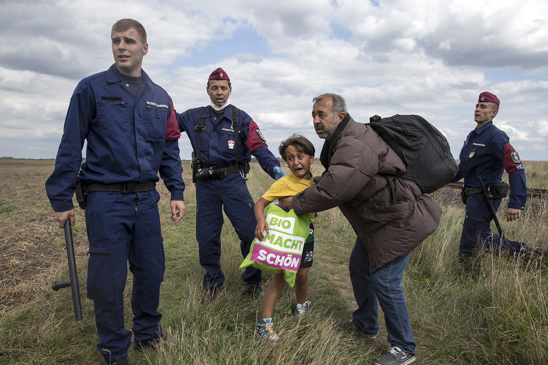 Hungarian police officers stop migrants as they try to escape on a field nearby a collection point in the village of Roszke, Hungary, September 8, 2015. REUTERS/Marko Djurica - RTX1RMHD