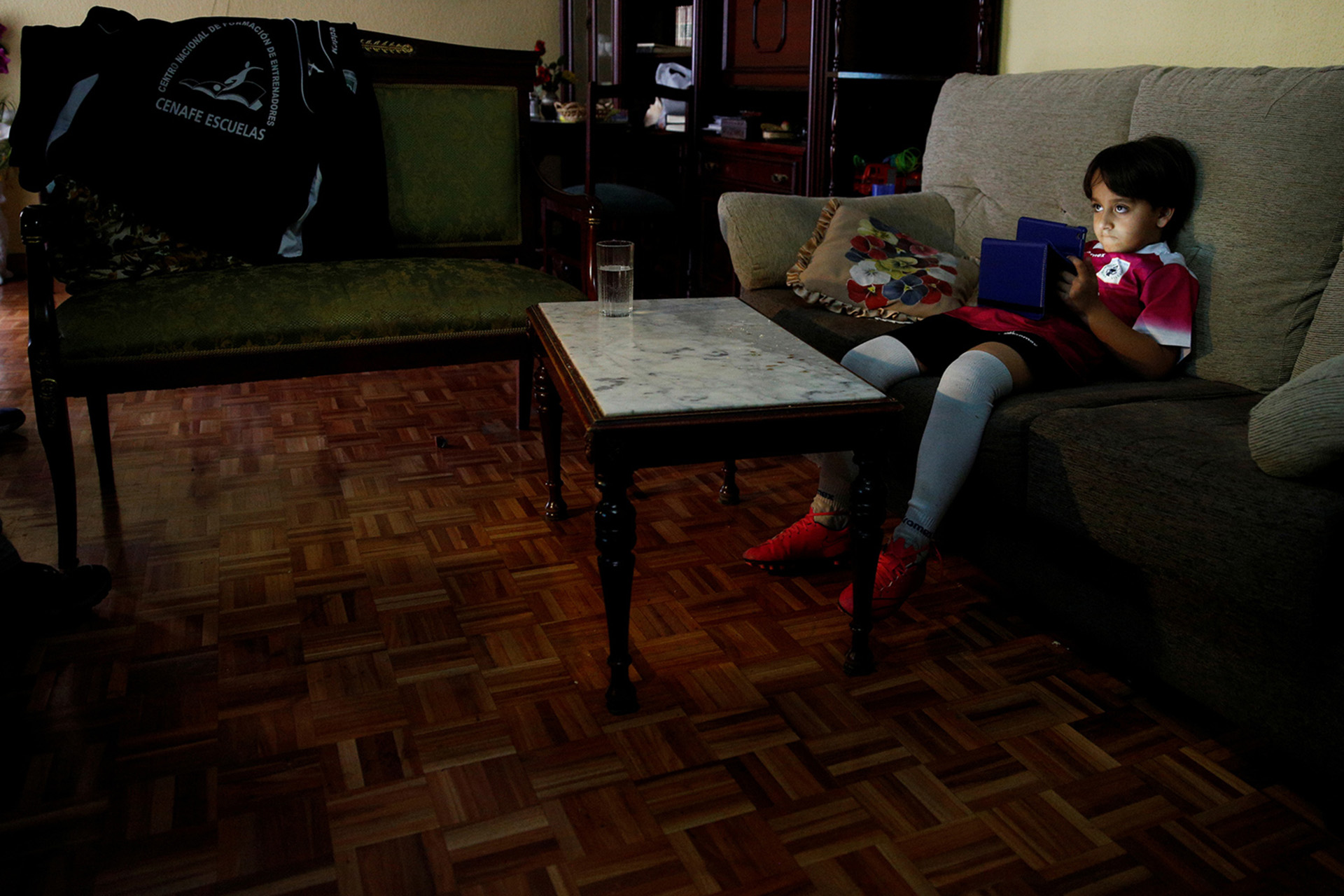 """ATTENTION EDITORS: SPANISH LAW REQUIRES THAT THE FACES OF MINORS ARE MASKED IN PUBLICATIONS WITHIN SPAIN - Zaid, the young son of Osama Abdul Mohsen, sits on a sofa at their home in Getafe, outside Madrid, Spain, April 14, 2016. Mohsen's story went viral after he was filmed being tripped up by a camerawoman as he fled police near the Hungarian border with Serbia last September. He was carrying his youngest son Zaid in his arms at the time, and the two fell sprawling on the ground. Footage of the incident helped bring him to the attention of a soccer training school in Getafe on the outskirts of Madrid, which found him work as a liaison officer. REUTERS/Sergio Perez     SEARCH """"REFUGEE PEREZ"""" FOR THIS STORY. SEARCH """"THE WIDER IMAGE"""" FOR ALL STORIES - RTX2CXCI"""