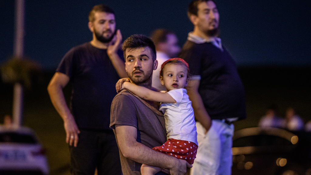 EDITORS NOTE: Graphic content / A man carries his daughter outside as people leave the airport after two explosions followed by gunfire hit the Turkey's biggest airport of Ataturk in Istanbul, on June 28, 2016. 