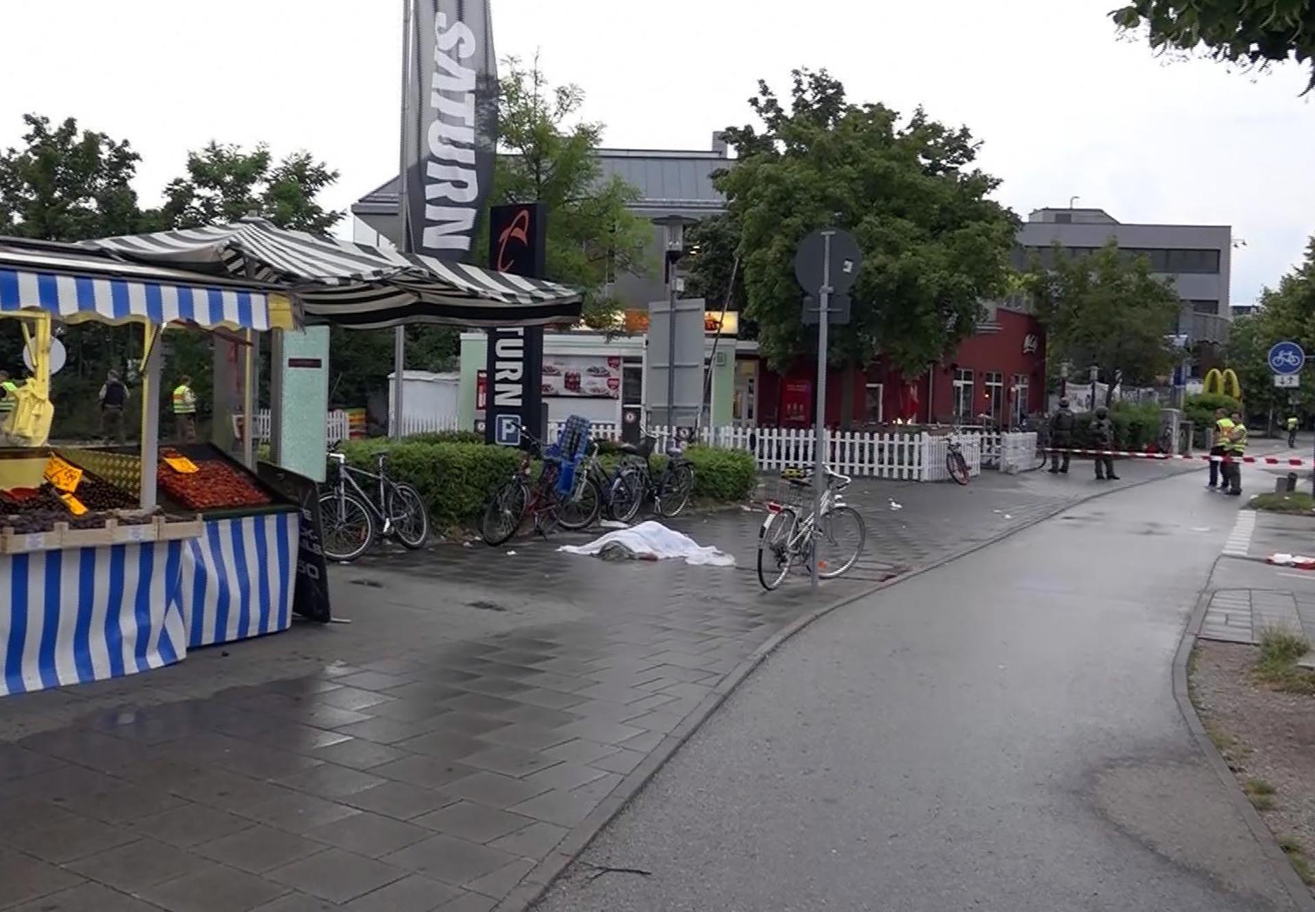 GERMANY OUT In this grab taken from video, a body covered with a sheet outside the mall, in Munich, Germany, Friday,  July 22, 2016. A manhunt was underway Friday for a shooter or shooters who opened fire at a shopping mall in Munich, killing and wounding several people, a Munich police spokeswoman said. The city transit system shut down and police asked people to avoid public places. (NONSTOP NEWS via AP)