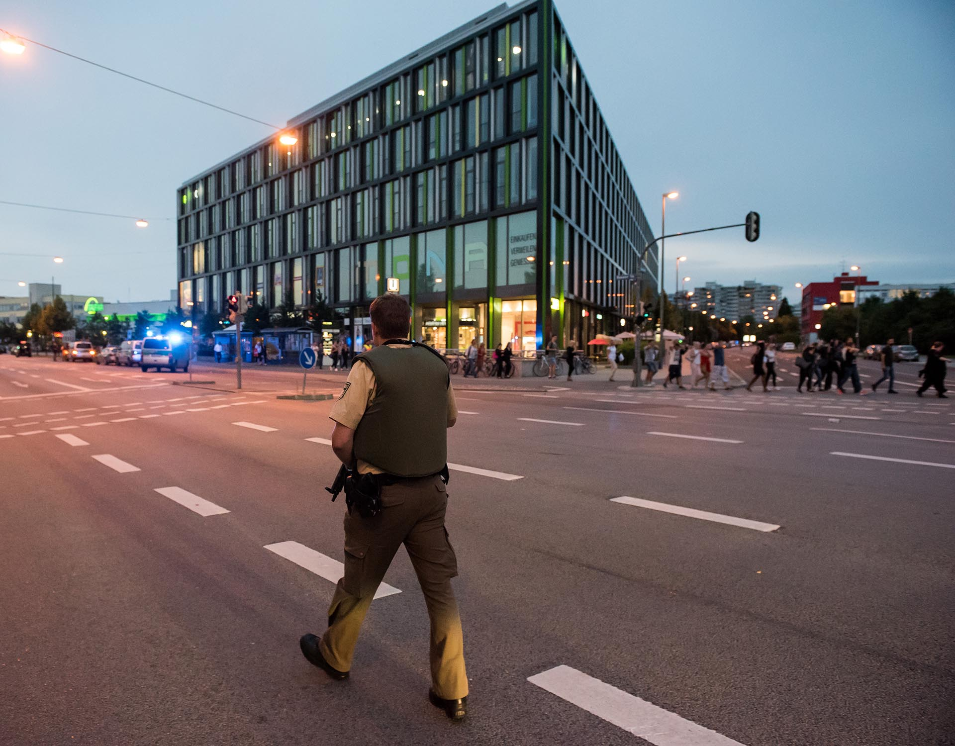 A policeman patrols as people are beeing evacuated (R) from a shopping mall in Munich on July 22, 2016 following a shooting earlier.