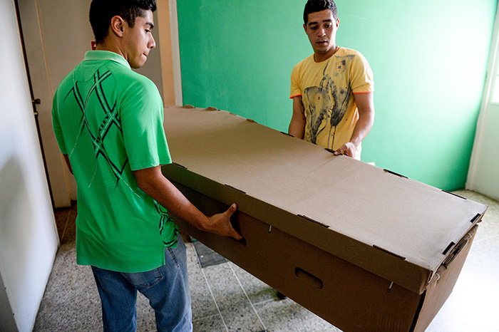 Two young men carry a cardboard coffin in Barquisimeto, Venezuela on August 9, 2016.