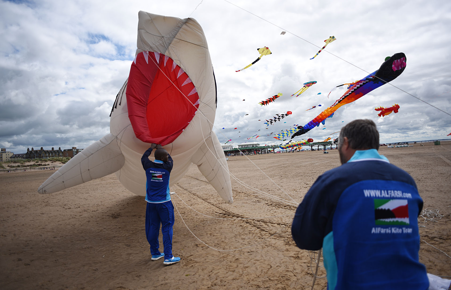 Members of the Kuwaiti Al Farsi Kite Team send up a shark kite as they participate in the St Annes Kite Festival on the seafront in Lytham St Annes, north west England on July 30, 2016. / AFP PHOTO / OLI SCARFF
