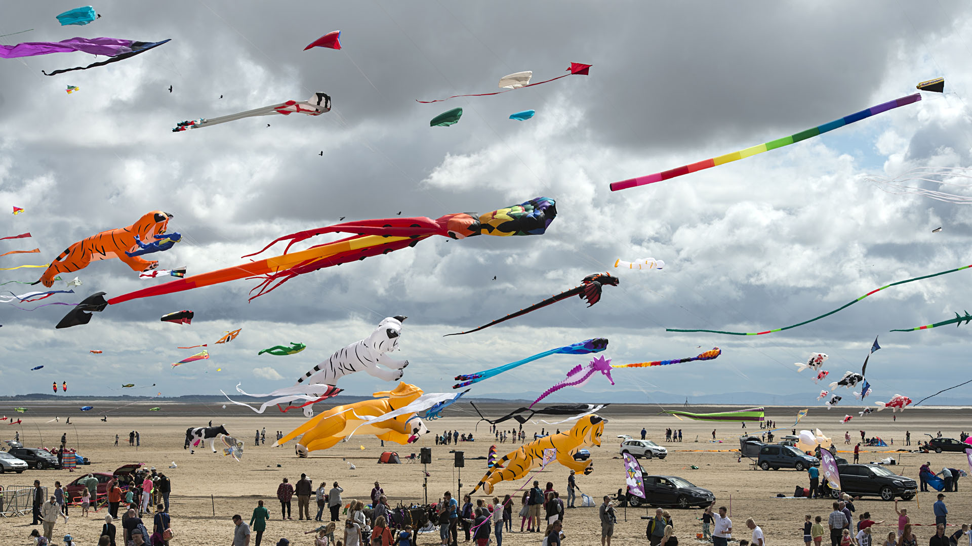 Members of the public relax on the beach as kite enthusiasts participate in the St Annes Kite Festival on the seafront in Lytham St Annes, north west England on July 30, 2016. / AFP PHOTO / OLI SCARFF