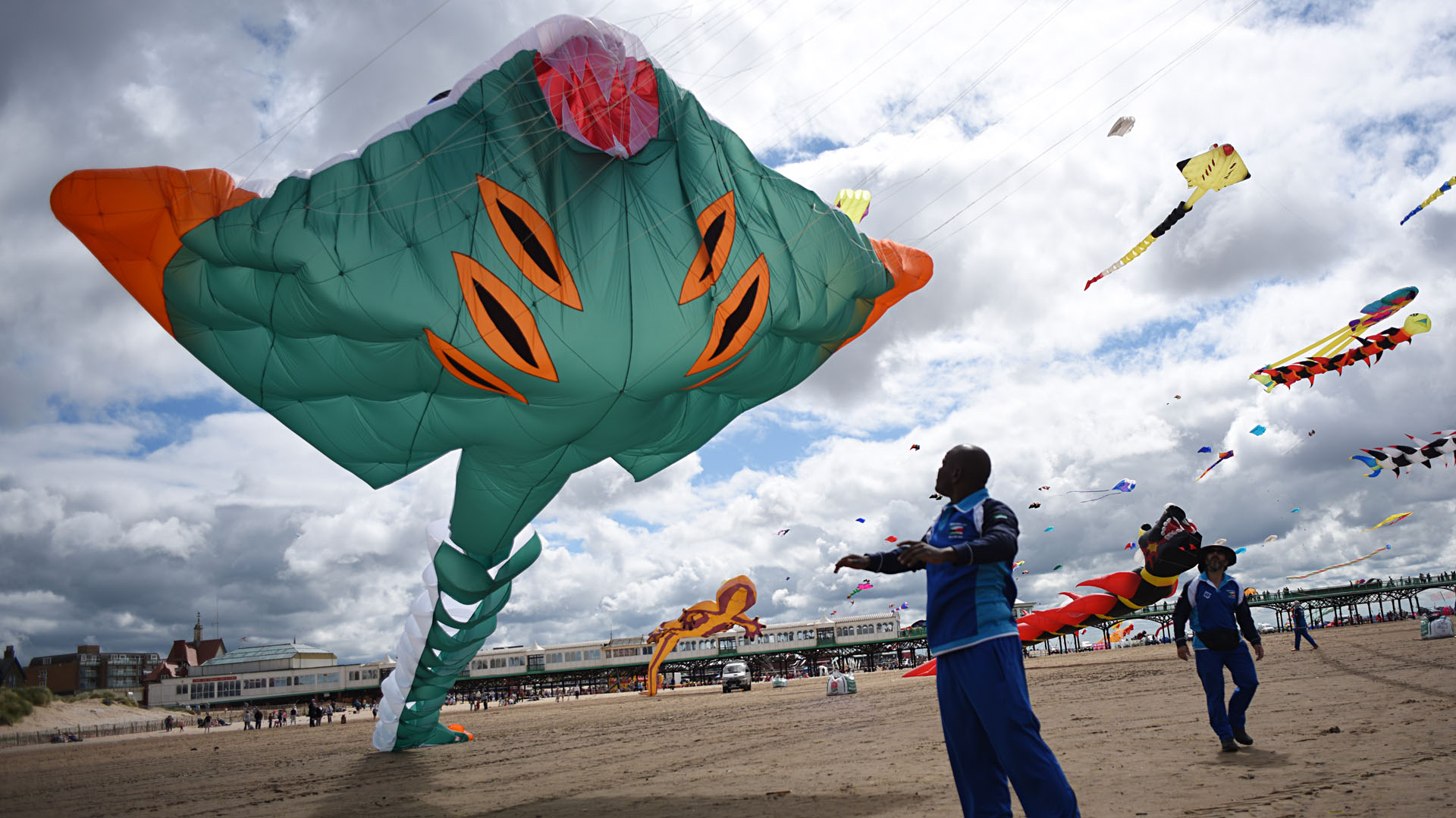 Members of the Kuwaiti Al Farsi Kite Team send up a kite as they participate in the St Annes Kite Festival on the seafront in Lytham St Annes, north west England on July 30, 2016. / AFP PHOTO / OLI SCARFF