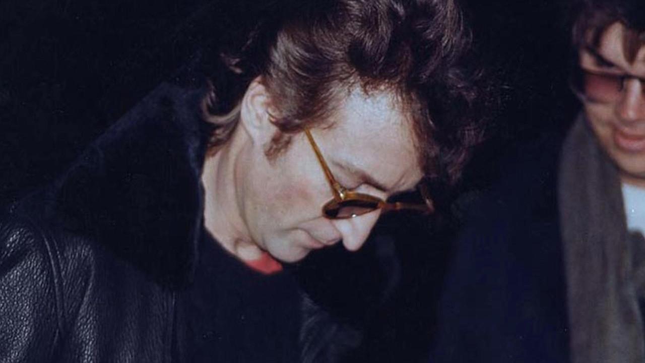 John Lennon fue fotografiado minutos antes de ser asesinado en el año 1980 en Nueva York (EE.UU.). El hombre que aparece a su derecha es Mark David Chapman, un admirador del ex Beatle, que acabó, lo asesinó minutos después.