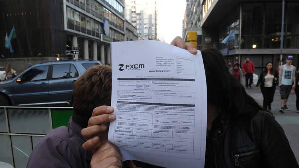 Las víctimas de Viglione posan con el formulario que les dio a cambio de su dinero. No quisieron mostrar sus rostros.