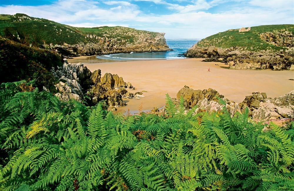 Playa de Cué. Llanes (Asturias): hasta 40 playas se reparten por el litoral del concejo de Llanes, una franja declarada Paisaje Protegido de la Costa Oriental asturiana. Algunas son arenales de la desembocadura de ríos (Guadamía, la Huelga), otras son medialunas doradas como la de Torimbio o plácidas aperturas entre acantilados y cañones (La Canal, San Martín).