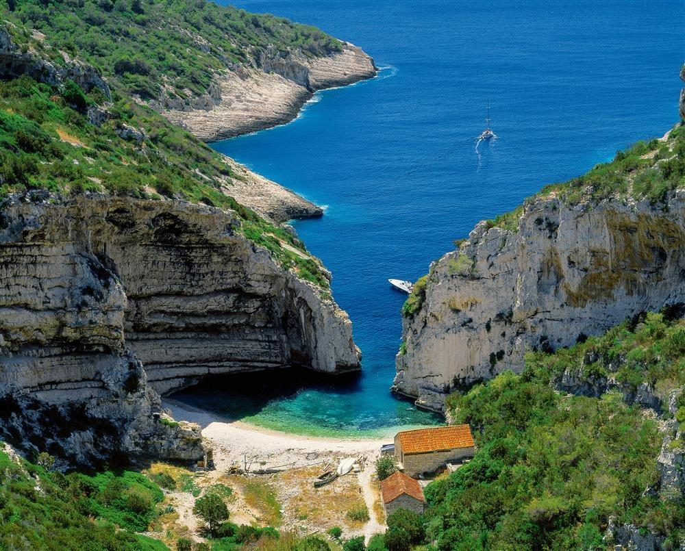 Playa Stiniva, Croacia: escondida entre formaciones de roca calcárea que la vuelven casi invisible desde el mar, esta playa de piedras blancas se cuenta entre las más atractivas de la Costa Dálmata croata.