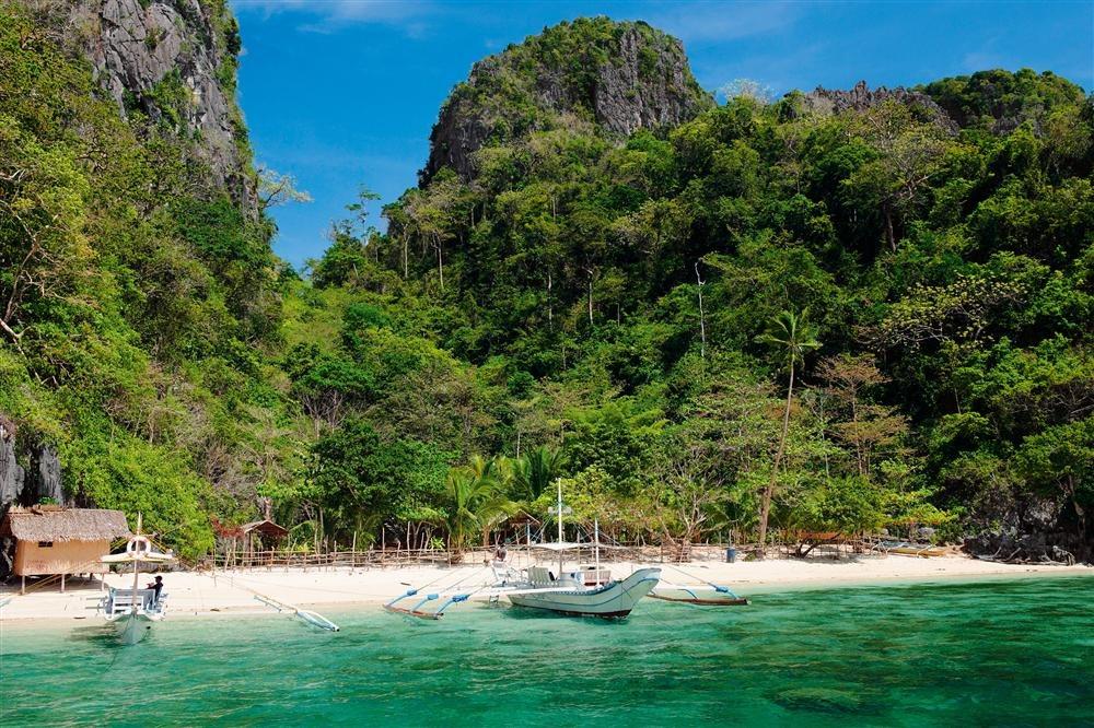 El Nido. Filipinas: la isla de Palawan, entre el mar de China y el mar de Sulu, tiene en El Nido un paisaje espectacular: un ojo de agua rodeado por un circo de acantilados tapizados de selva hasta la misma orilla. Desde las solitarias playas de esta área protegida del oeste de Filipinas, se ve cómo el cielo límpido cambia el color del agua a lo largo del día, sacando destellos de un fondo marino rico en vegetación y fauna.