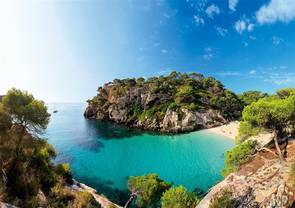 Cala Macarelleta, Menorca: la costa sur de la isla balear reúne calas de arenas blancas abrazadas por pinos que se asoman al agua desde las rocas. Cala Macarella y su hermana pequeña, Macarelleta, son un excelente ejemplo de este paisaje mediterráneo.