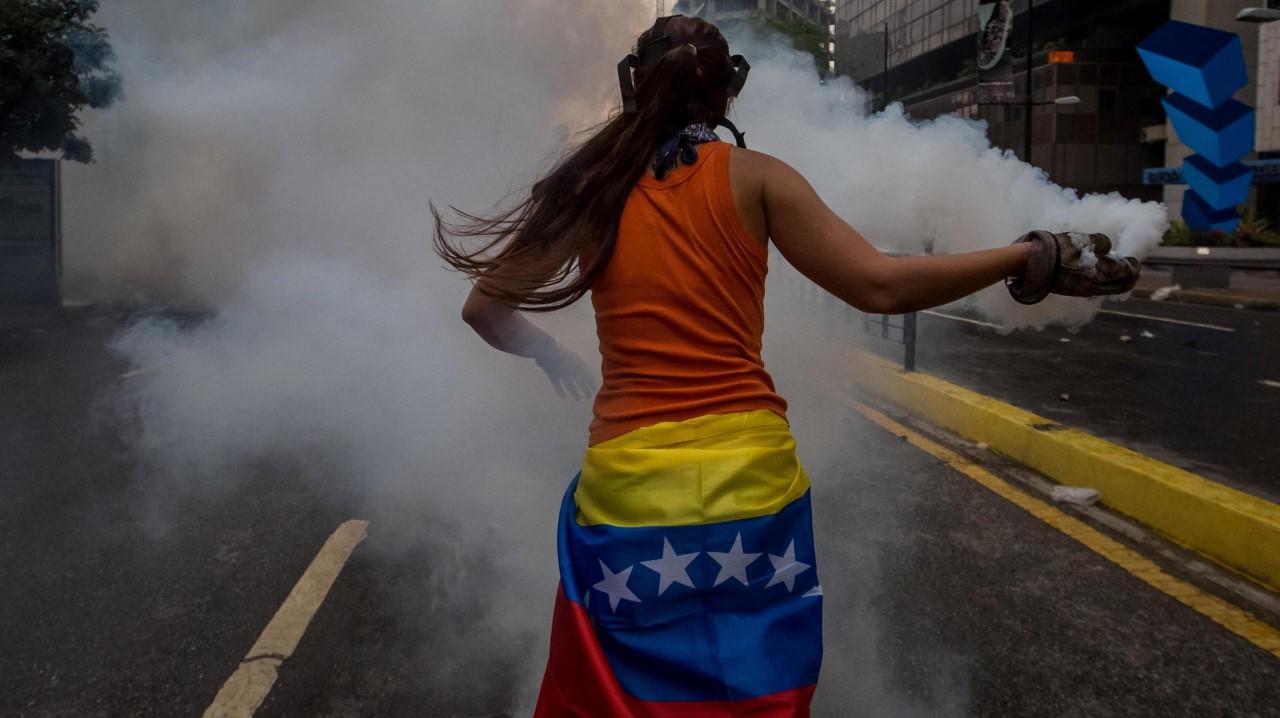 Una mujer venezolana devuelve una granada lacrimógeno lanzada por agentes de la Guardia Nacional Bolivariana, en Caracas, Venezuela. La Guardia Nacional de Venezuela (GNB, policía militarizada) dispersó con gases lacrimógenos algunas concentraciones de opositores que se congregaban en diversos puntos de Caracas para marchar hacia la Defensoría del Pueblo, en el centro de la capital.