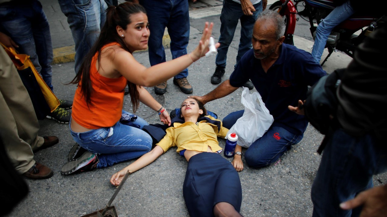 Una mujer es ayudada por otros manifestantes después de caer desvanecida por los gases lacrimógenos