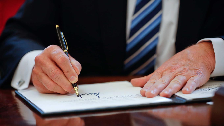Donald Trump firma un documento en la Casa Blanca durante el encuentro con Mauricio Macri