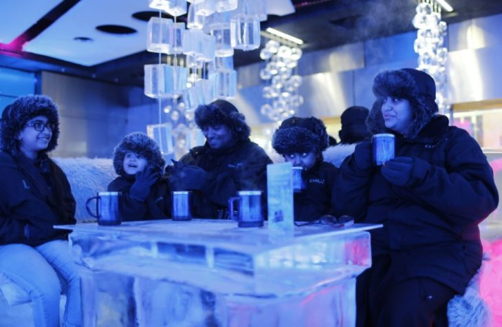 A Saudi Arabian family drinks hot chocolate at Chillout cafe in Dubai May 12, 2013. Chillout, owned by UAE's Sharaf Group, is the first ice lounge in the Middle East, with temperatures set at -6 degrees Celsius (21 degrees Farenheit). The cafe, with its illuminated interiors, curtains, paintings and seating arrangements, is all made of carved ice and frozen sculptures. Picture taken May 12, 2013. REUTERS/Ahmed Jadallah (UNITED ARAB EMIRATES - Tags: SOCIETY)