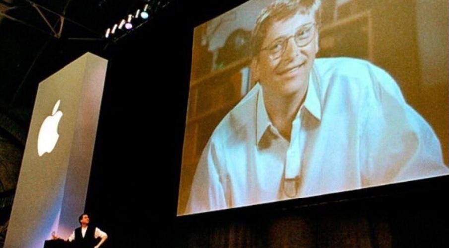 Bill Gates en videoconferencia durante el anuncio, con Steve Jobs en el escenario.