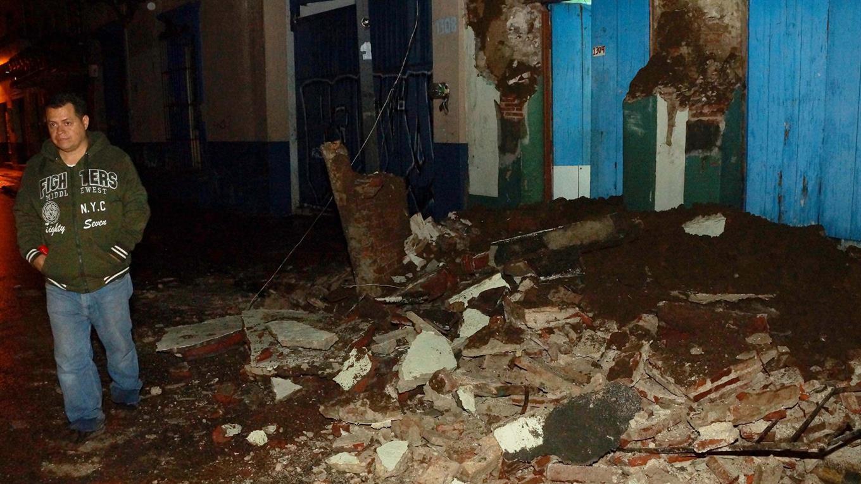 Un hombre pasa por al lado de un pila de escombros de una casa que quedó destrozada en Oxaca.