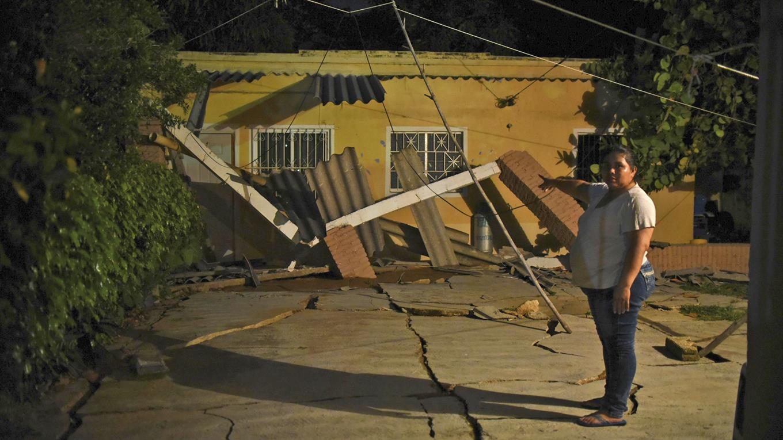 Un mujer muestra su casa fue atravesada por una grieta tras el sismo.