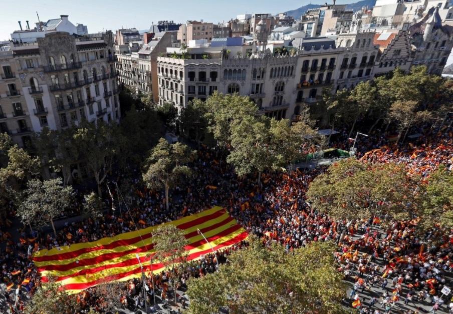 Manifestantes a favor de la unidad marchan por el Paseo de Gracia de Barcelona con una bandera de Cataluña.